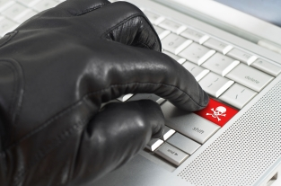 Hacker concept with hand wearing black leather glove pressing en