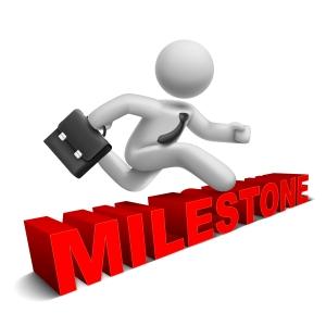 3d businessman jumping over 'milestone' word
