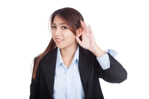 Young Asian businesswoman listen with hand on ear
