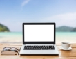 laptop computer and coffee on wood workspace and the beach background