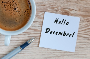 Hello December written on paper near morning coffee cup at